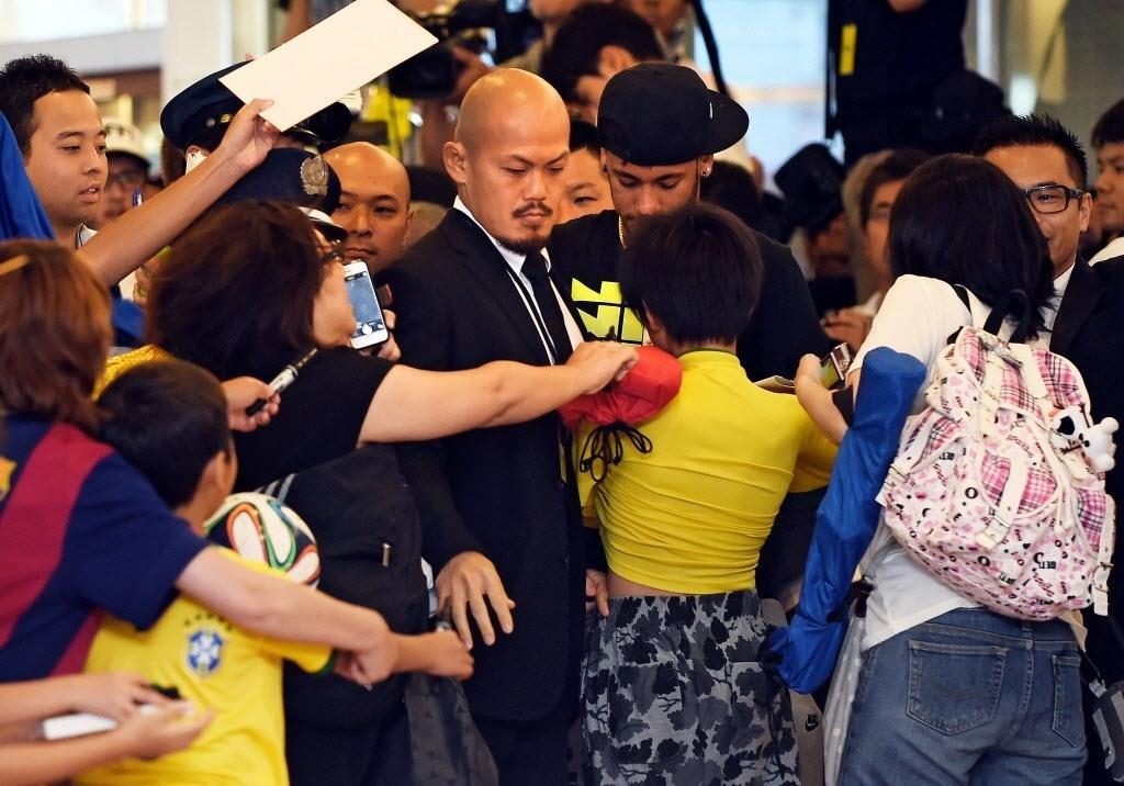 31.jul.2014 - Segurança tenta abrir caminho para Neymar na multidão que foi a aeroporto de Tóquio para receber o jogador