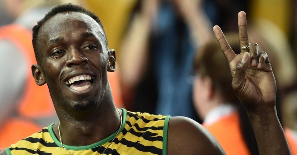 Usain Bolt acena após vencer com a Jamaica eliminatória do revezamento 4x100 m no Jogos da Comunidade Britânica