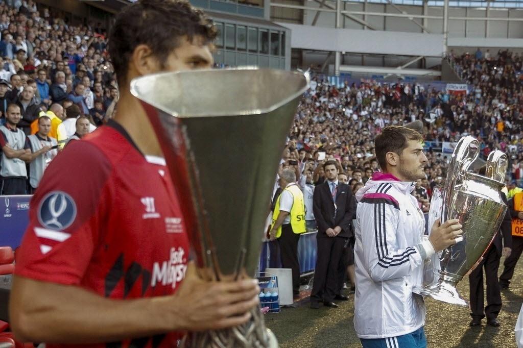 Fazio, capitão do Sevilla, entra em campo com a taça da Liga Europa; Casillas, capitão do Real Madrid, com a taça da Liga dos Campeões