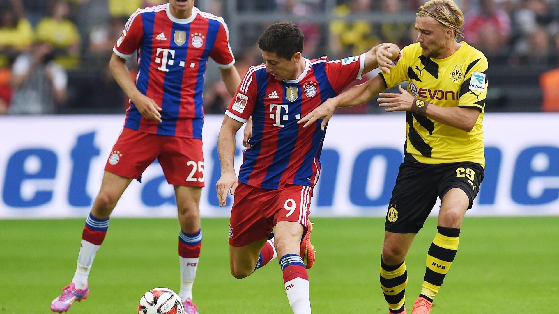 Agora atacante do Bayern de Munique Robert Lewandowski tenta se livrar da marcação do Borussia Dortmund, sua ex-equipe, na Supercopa da Alemanha