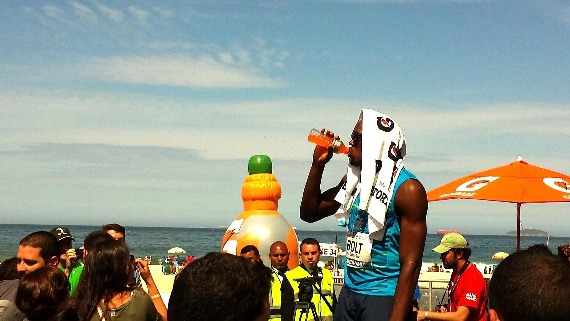 17.ago.2014 - O jamaicano Usain Bolt se refresca após vencer o desafio dos 100m no Rio de Janeiro
