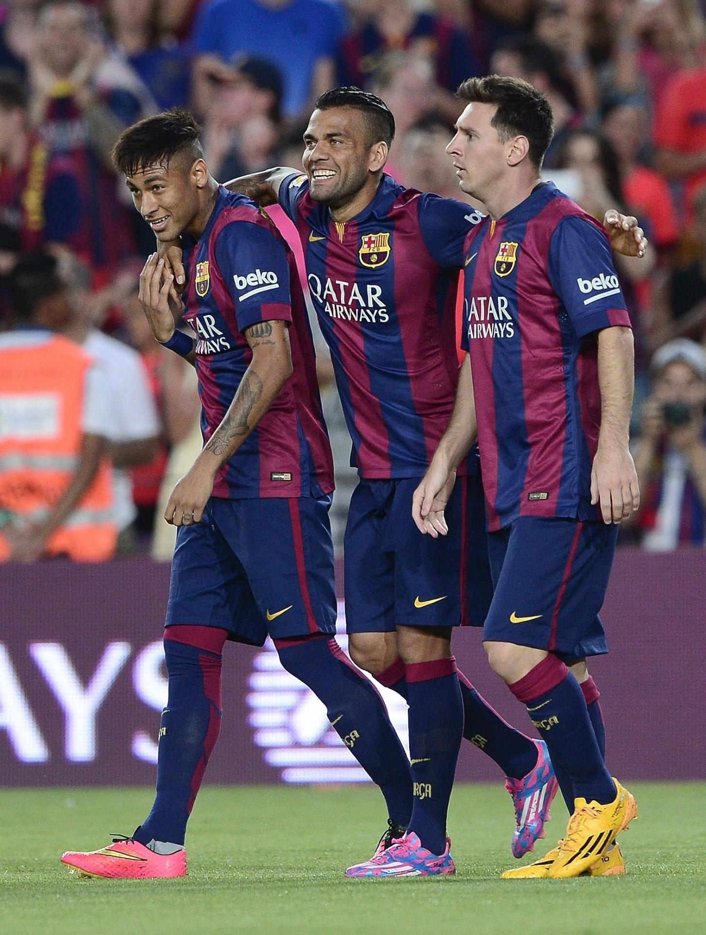 Messi é abraçado por Neymar e Daniel Alves após marcar o primeiro gol do Barcelona no troféu Joan Gamper, contra o León-MEX. O jogo marca a apresentação do elenco catalão à torcida.
