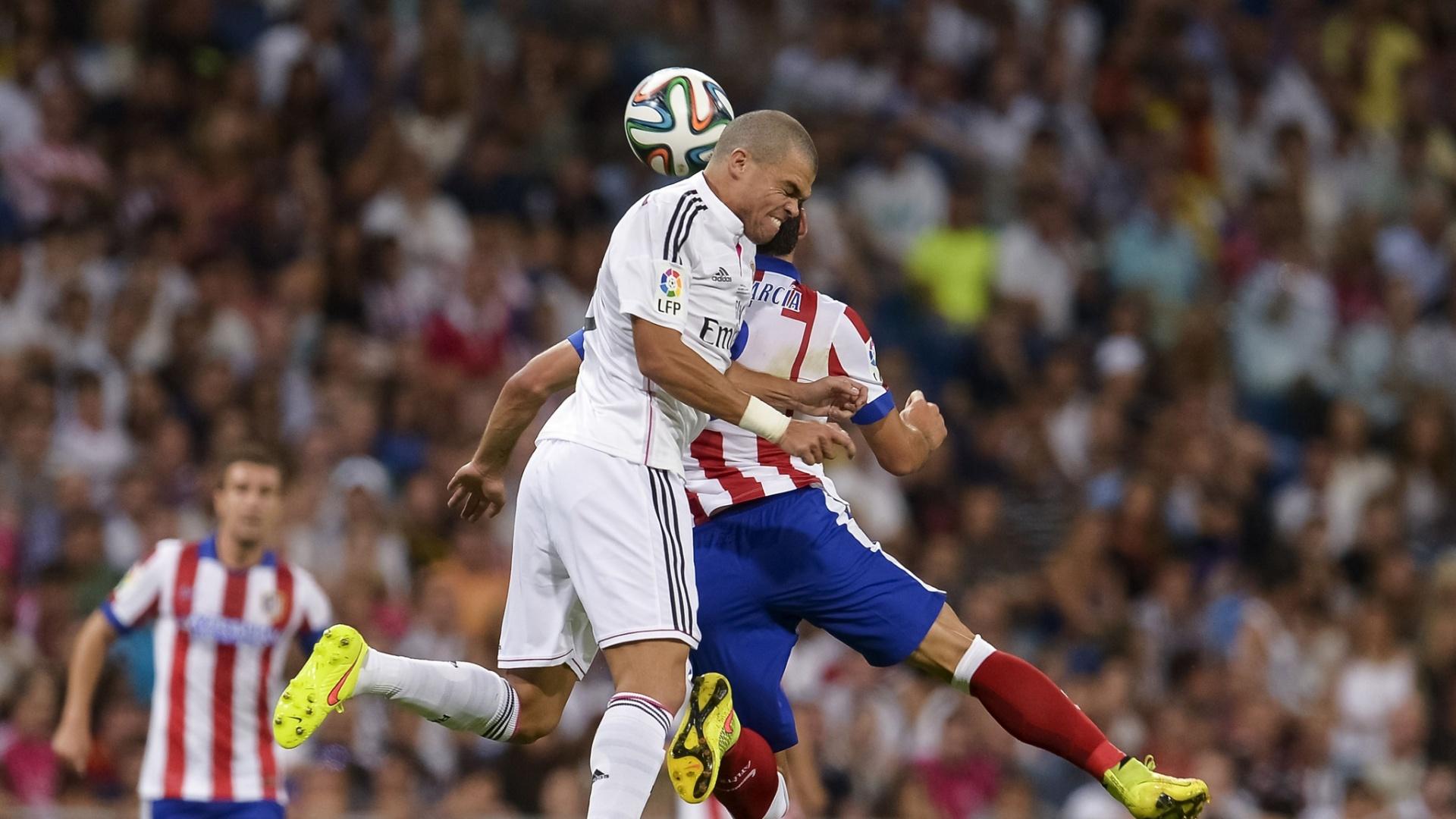 Zagueiro Pepe (frente) sobe de cabeça junto com Raul García no jogo entre Real x Atlético