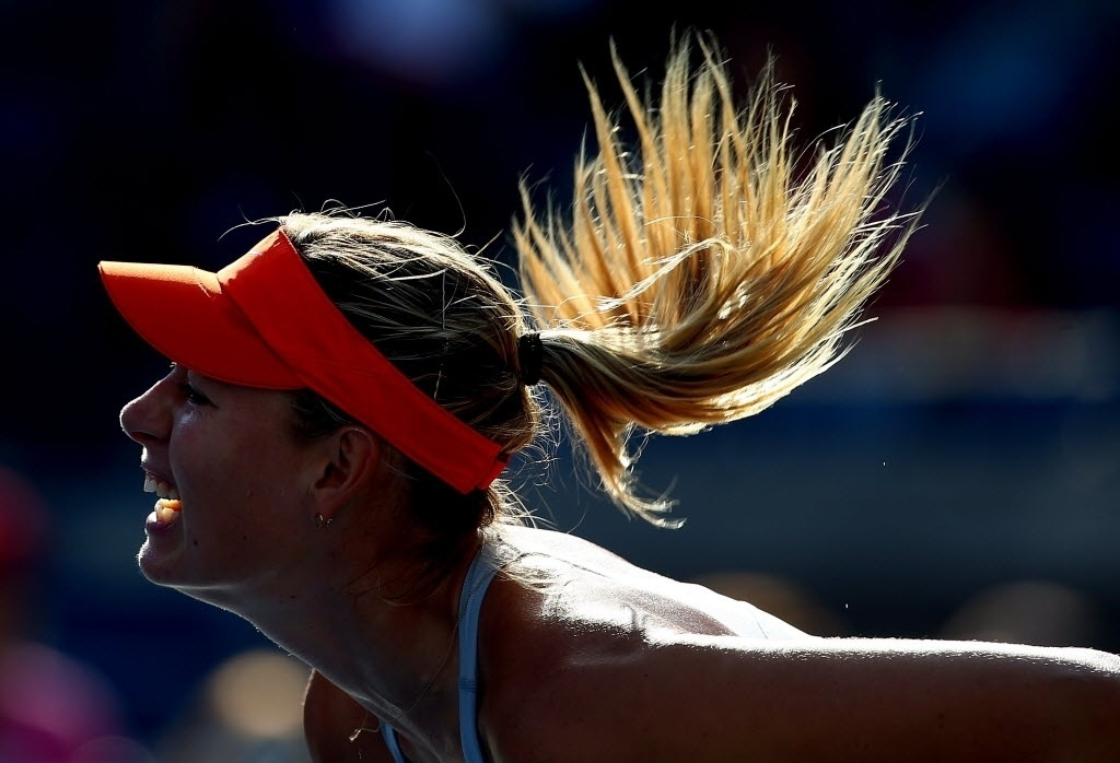 Cabelos de Maria Sharapova esvoaçam enquanto a russa saca no duelo com Alexandra Dulgheru