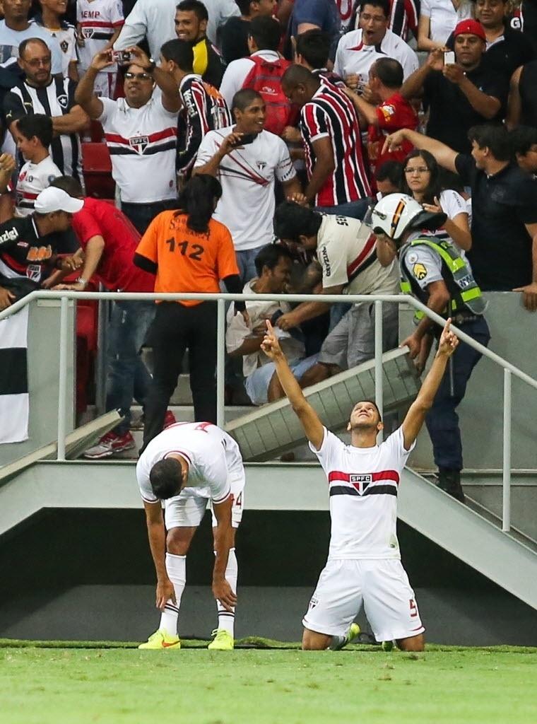 Souza comemora gol do São Paulo enquanto torcedor fica caído na arquibancada