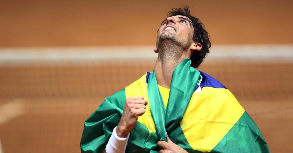 14.set.2014 - Enrolado na bandeira do Brasil, Bellucci comemora a vitória sobre Roberto Bautista que deu ao Brasil um lugar na elite do tênis mundial