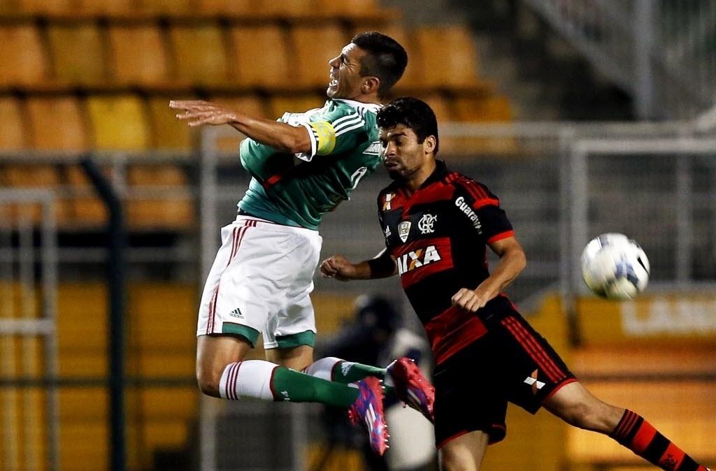 Lúcio e Eduardo da Silva disputam bola de cabeça na partida entre Flamengo e Palmeiras