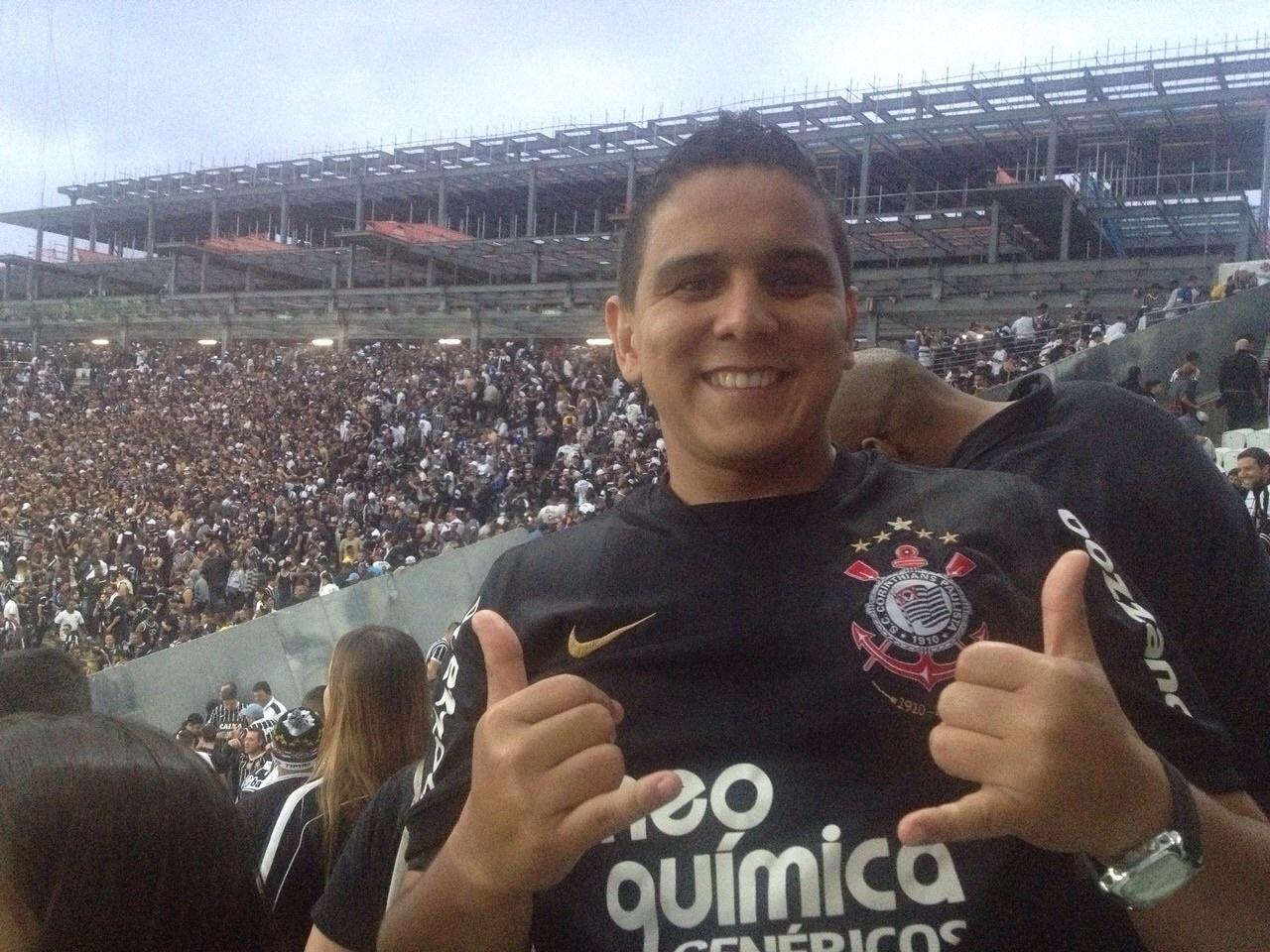 Torcedor do Corinthians posa para foto no clássico contra o São Paulo. Ao fundo, torcida lota o estádio