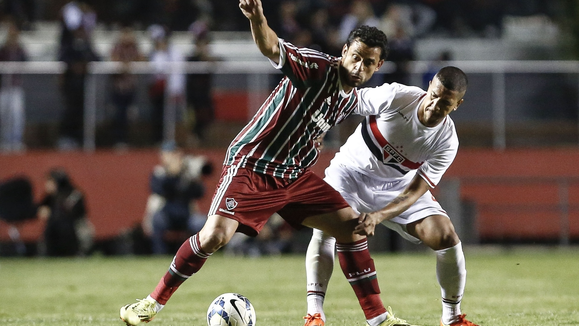 Fred usa o corpo para evitar marcação do zagueiro Antônio Carlos na partida contra o São Paulo