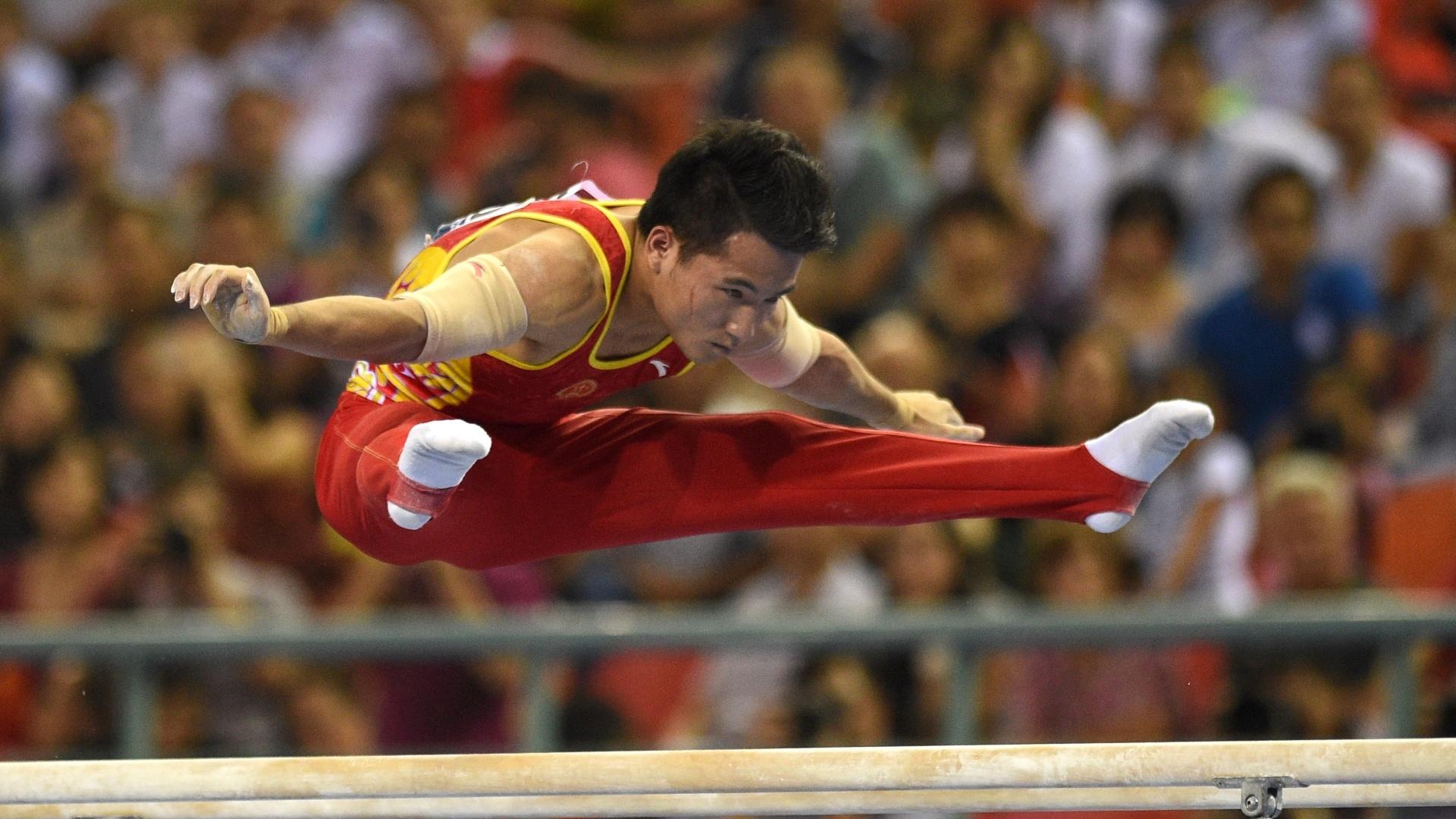 9.out.2014 - Deng Shudi, da China, faz sua exibição nas barras paralelas durante o Mundial de Ginástica Artística em Nanning (China)