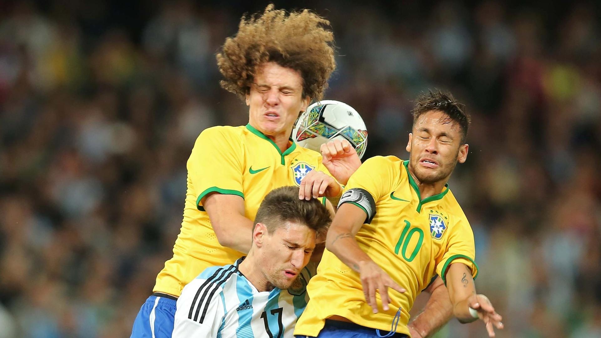 David Luiz e Neymar, da seleção brasileira, sobem de cabeça para brigar pelo alto com Fernandez, da Argentina, no Superclássico das Américas, em Pequim