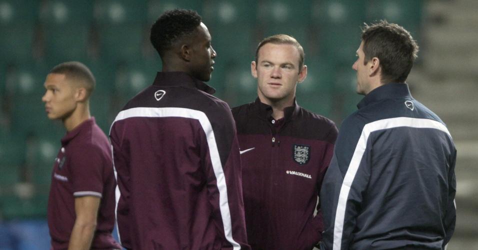 Rooney, atacante da Inglaterra, conversa com Welbeck (à esquerda) e um membro da comissão técnica no reconhecimento de gramado na Estônia; time entra em campo no domingo
