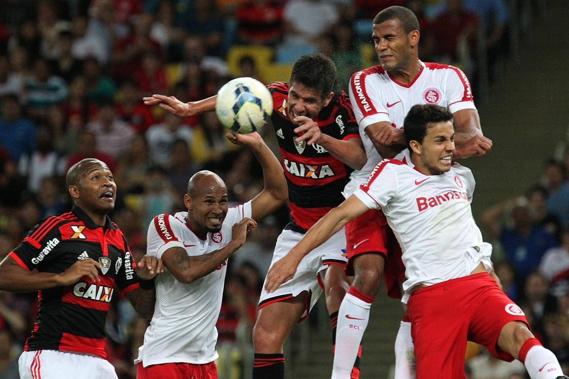 Jogadores de Flamengo e Inter disputam bola de cabeça em jogo do Brasileirão