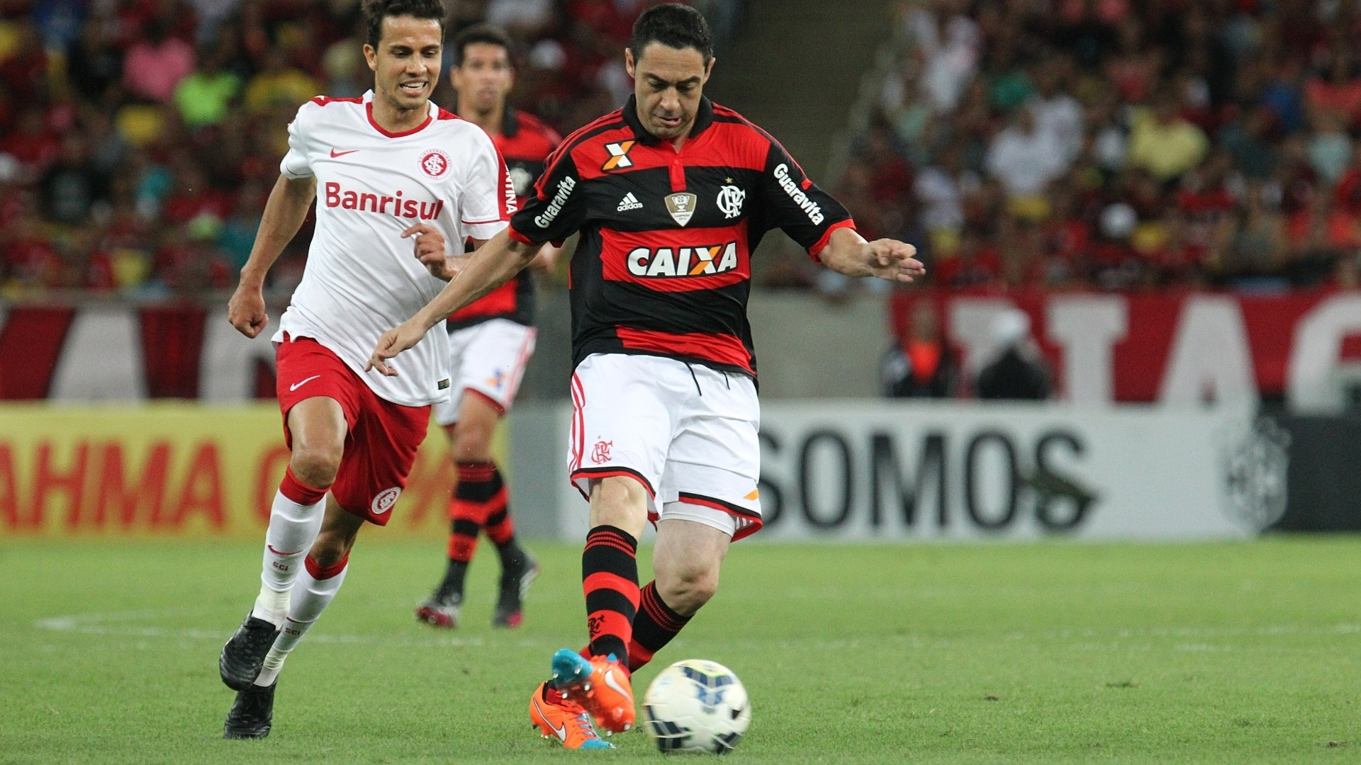 Nilmar tenta evitar que Chicão saia jogando no duelo entre Flamengo e Inter