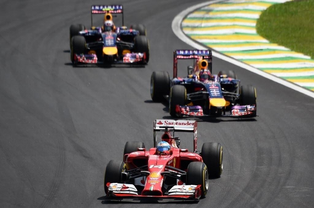Ferrari de Fernando Alonso perseguido pelos dois carros da Red Bull no GP Brasil