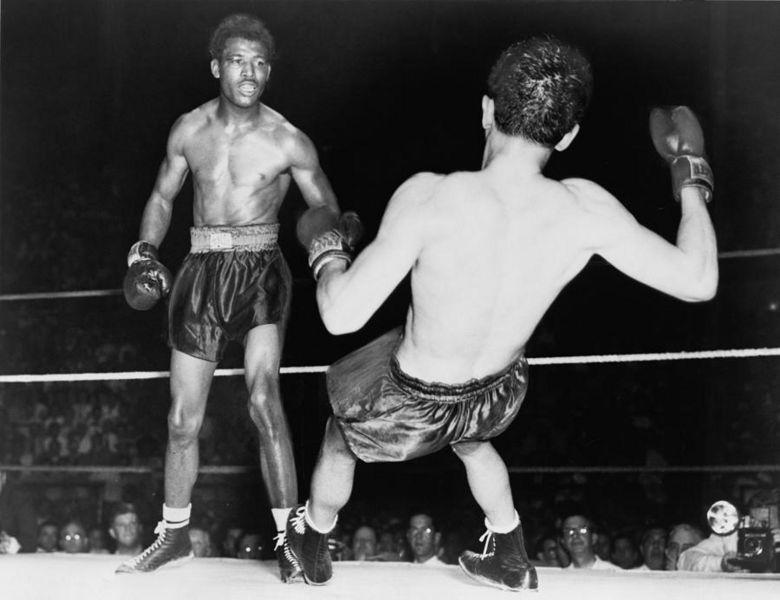 Sugar Ray Robinson observa a queda de Jimmy Doyle na trágida luta de 1947