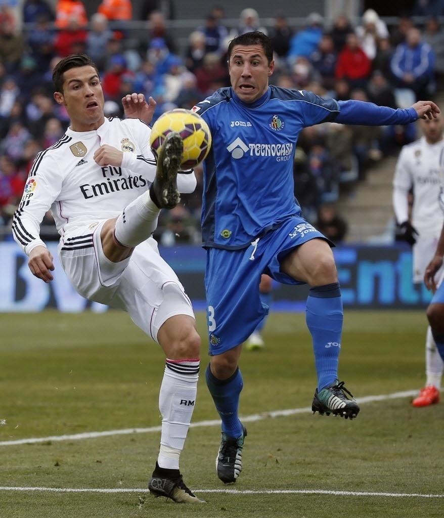 18.jan.2015 - Cristiano Ronaldo disputa bola com Roberto Lago, do Getafe, durante partida do Campeonato Espanhol neste domingo (18)