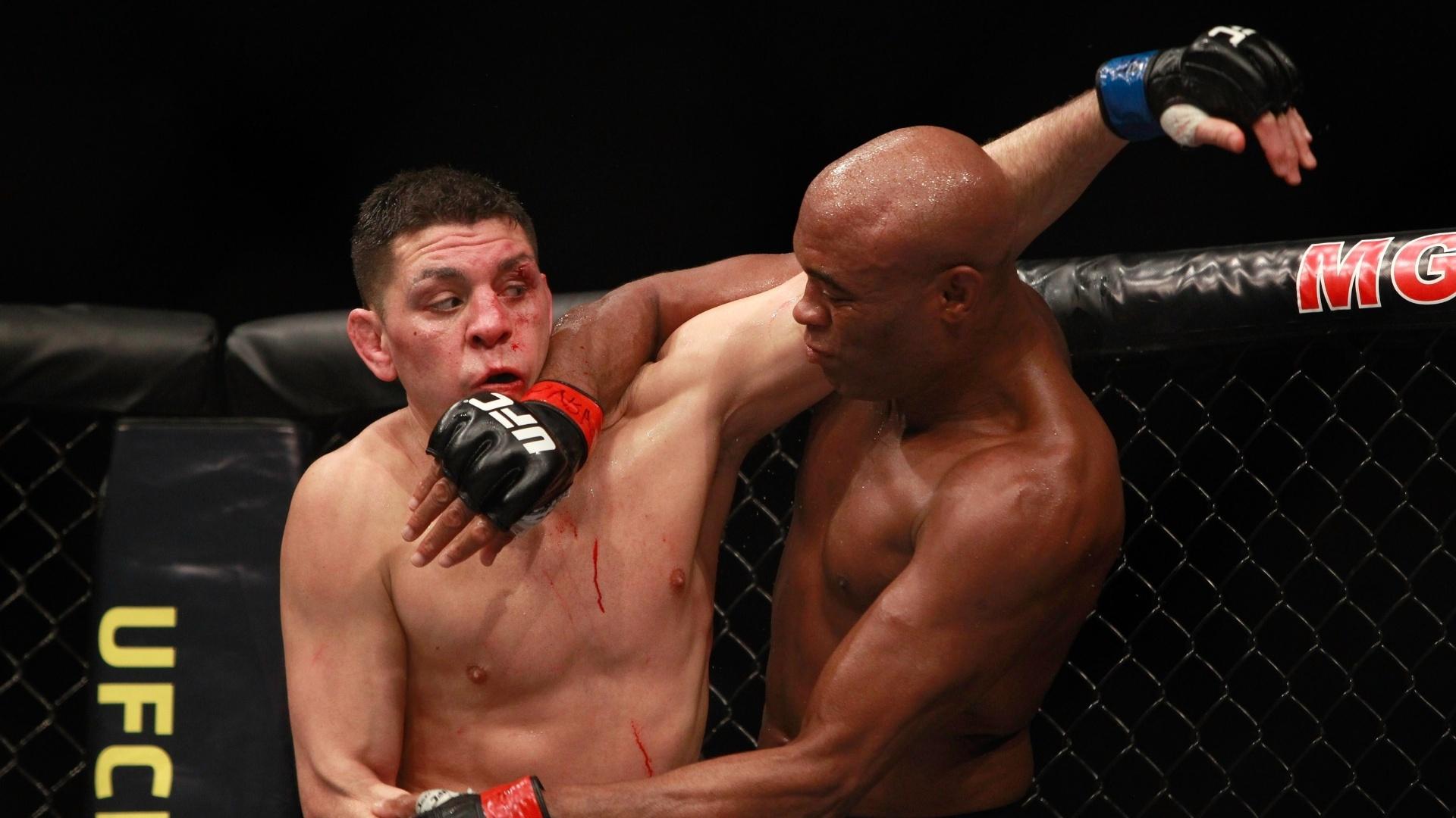 Com o rosto machucado, Nick Diaz tenta se livrar da investida de Anderson Silva durante a luta principal do UFC 183 em Las Vegas (EUA)