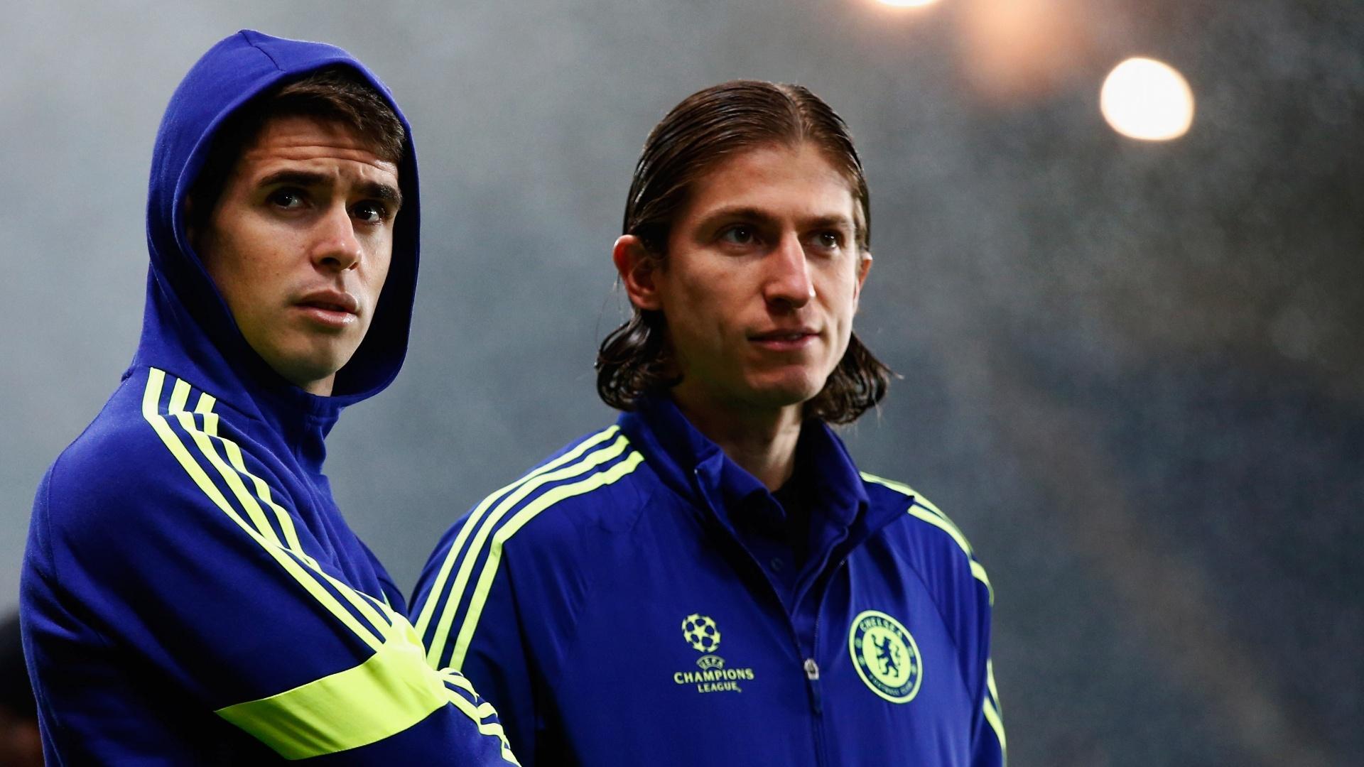 Oscar e Filipe Luis, jogadores do Chelsea, assistem ao jogo contra o PSG, pela Liga dos Campeões, do banco de reservas do clube inglês