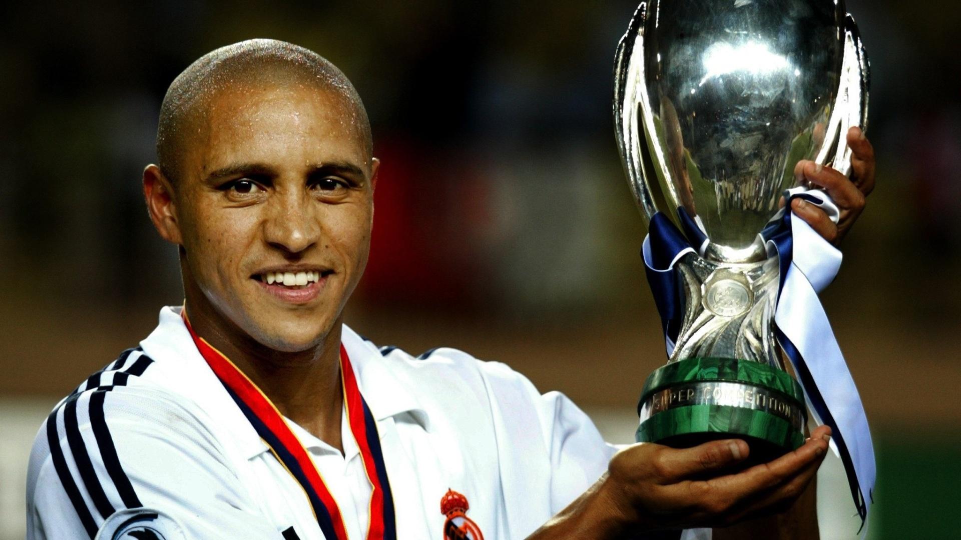 Roberto Carlos, lateral do Real Madrid, segura troféu da Supercopa da Europa, conquistado contra o Feyenoord em 2002.