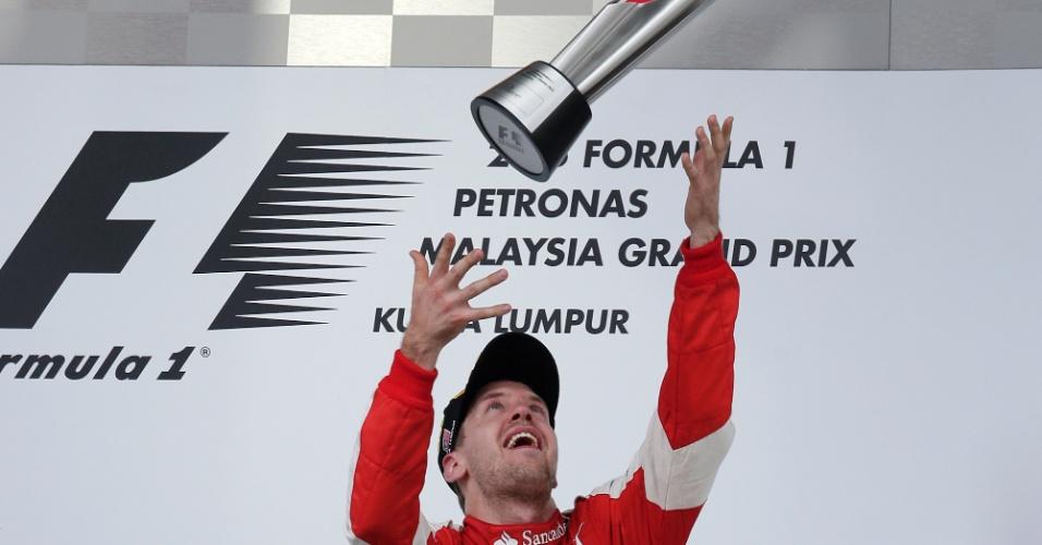 Sebastian Vettel comemora vitória no GP da Malásia jogando o troféu para o alto