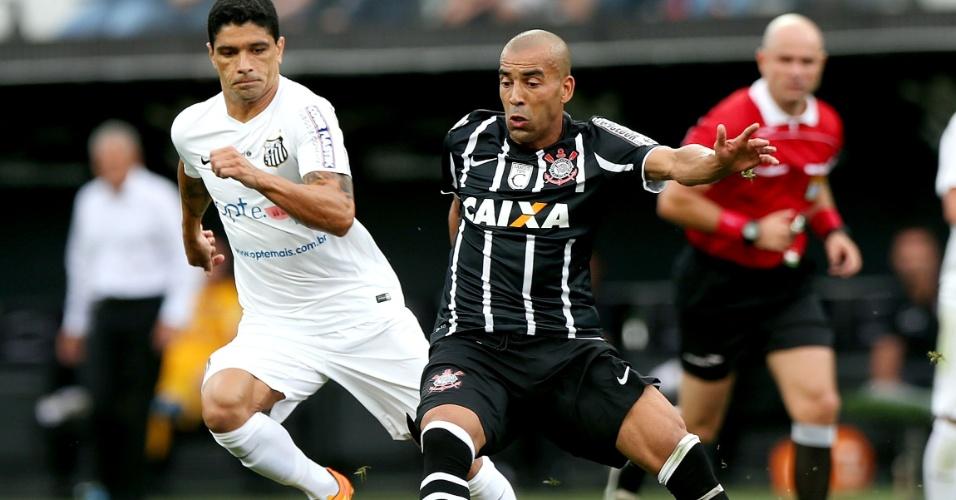 Emerson, do Corinthians, tenta o passe observado de perto por Renato, do Santos, durante clássico pelo Camp. Paulista