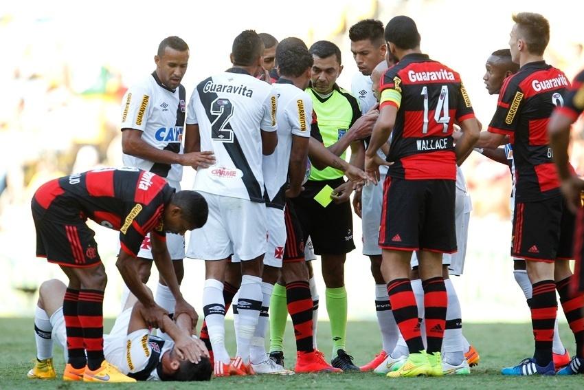 Jogadores de Flamengo e Vasco cercam o árbitro em uma das muitas reclamações