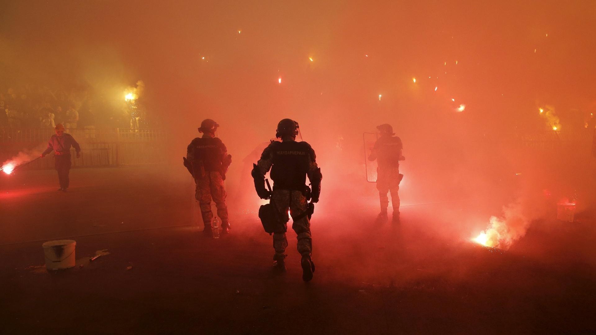 Policiais recolhem sinalizadores do gramado após a paralisação do clássico entre Estrela Vermelha e Partizan, na Sérvia
