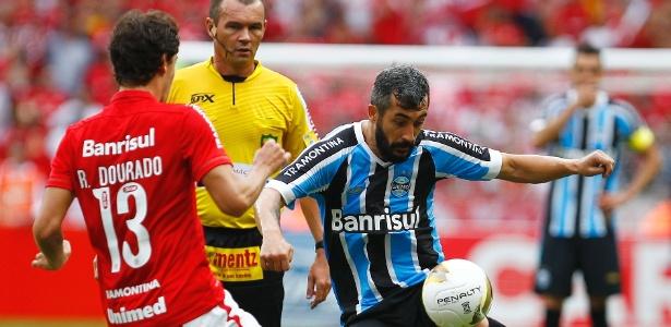 Douglas, do Grêmio, tenta fugir da marcação de Rodrigo Dourado, do Internacional