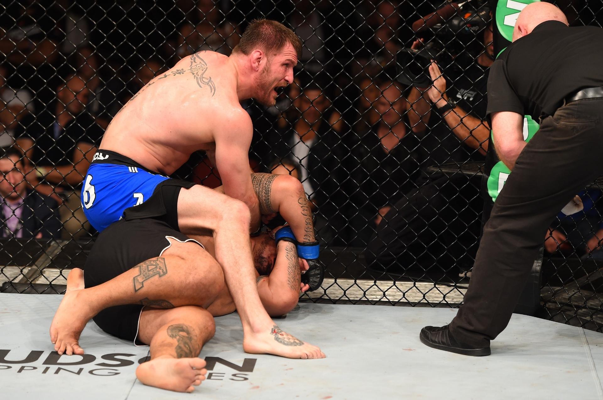 Stipe Miocic olha para árbitro enquanto Mark Hunt se protege durante luta principal do UFC: Miocic x Hunt