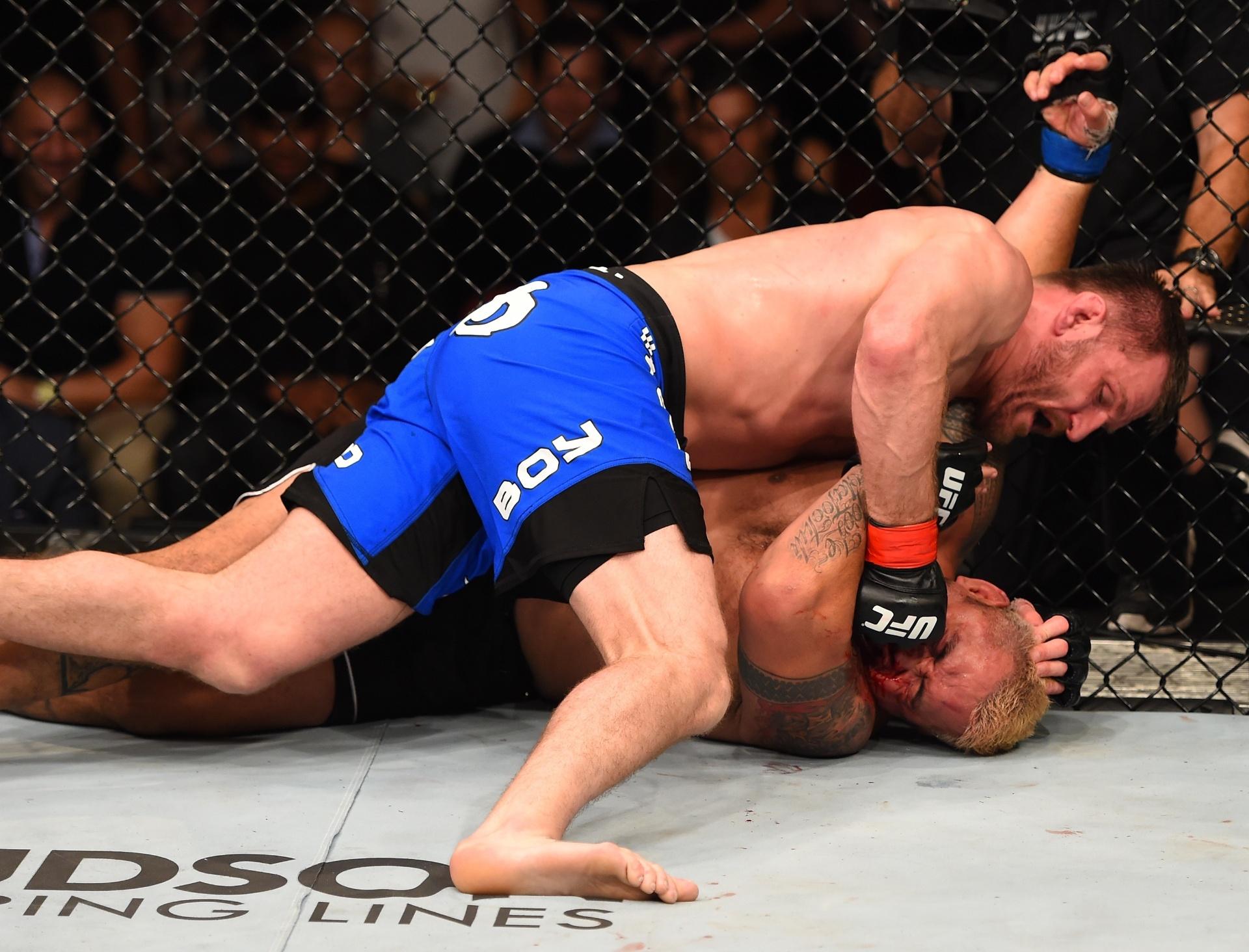Stipe Miocic (por cima) aplica golpe no rosto de Mark Hunt durante UFC: Miocic x Hunt, realizado na madrugada deste domingo (10), na Austrália