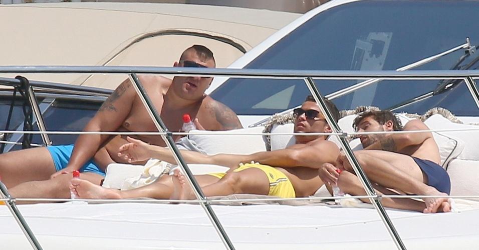 O atacante do Real Madrid descansa com os amigos enquanto pega o sol do verão Europeu