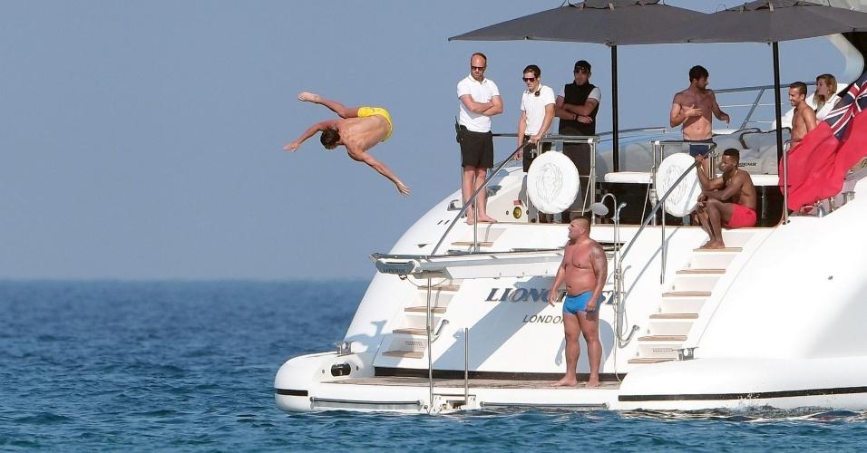 O português faz pose enquanto salta do trampolim do iate