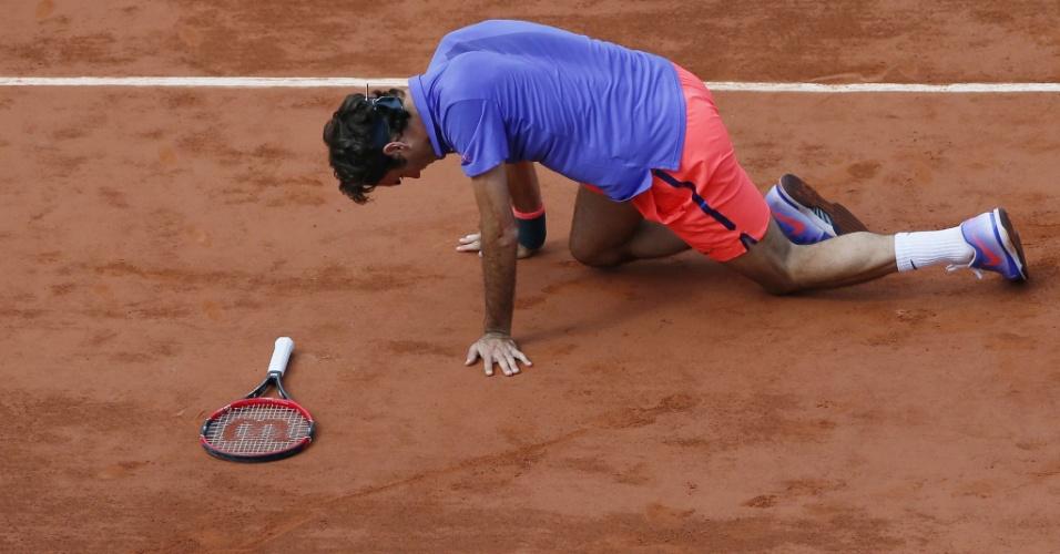 Federer caiu na quadra após rebater uma bola na partida contra Wawrinka