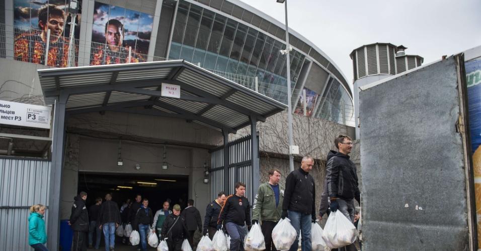 Pôsteres de Bernard e Alex Teixeira pendurados no estádio enquanto voluntários levam comidas para os caminhões