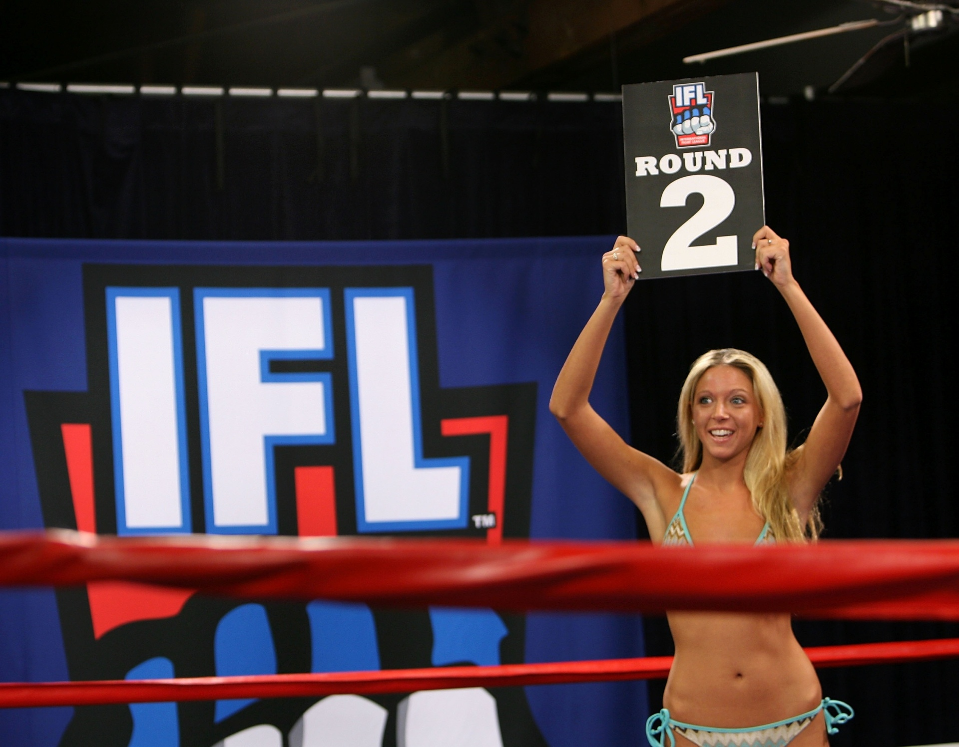 Ring girls de biquíni são comuns em eventos de boxe
