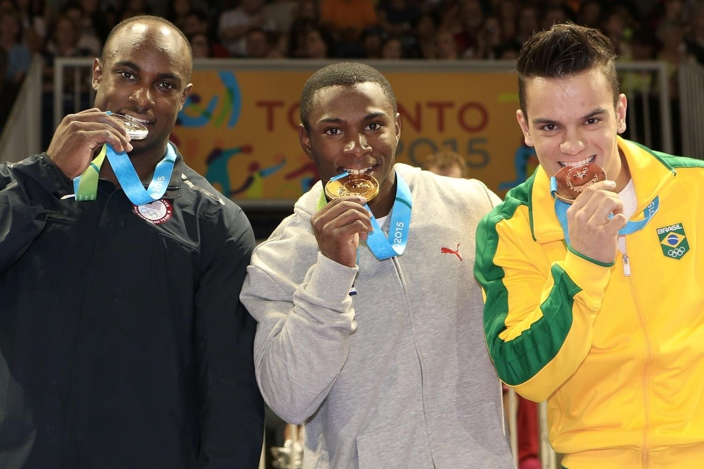 Ao lado do americano Donnell Whittenburg e do cubano Manrique Larduet, prata e ouro, respectivamente, Caio Souza morde a medalha de bronze conquistada no salto sobre a mesa