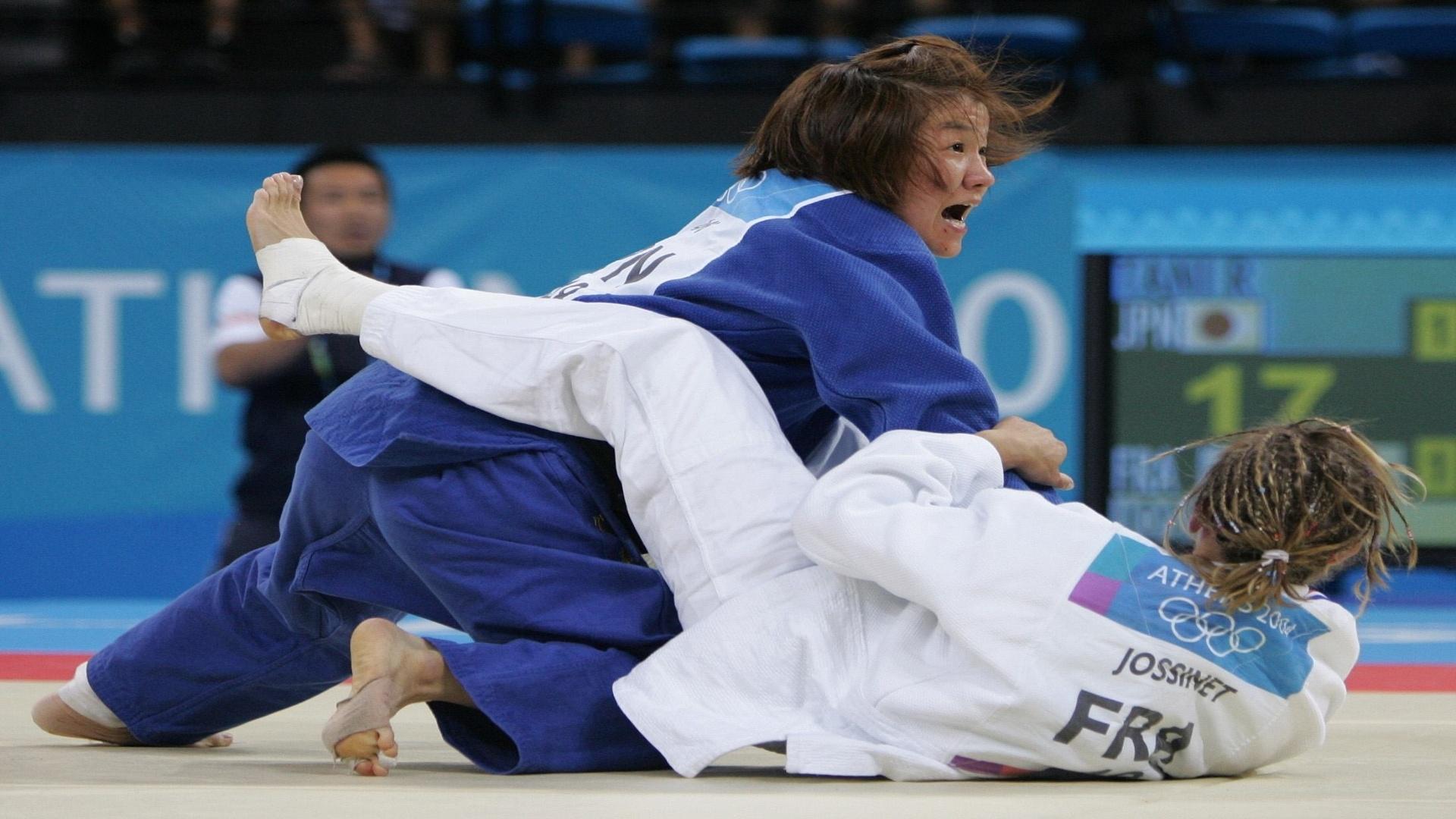 14.ago.2004 - Japonesa Ryoko Tamura Tani aplica um golpe na francesa Frederique Jossinet na disputa do judô na Olimpíada de Atenas