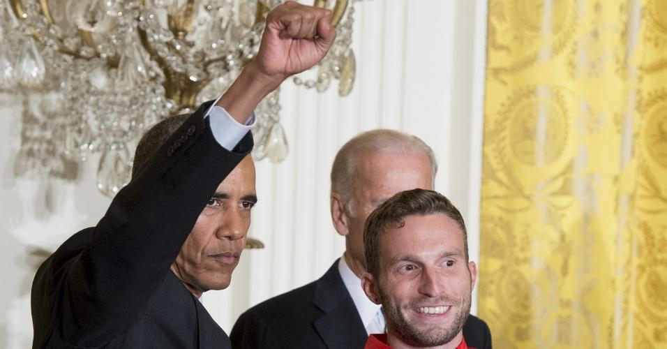 Barack Obama ergue o punho direito como os Panteras Negras durante cerimônia com atletas olímpicos na Casa Branca
