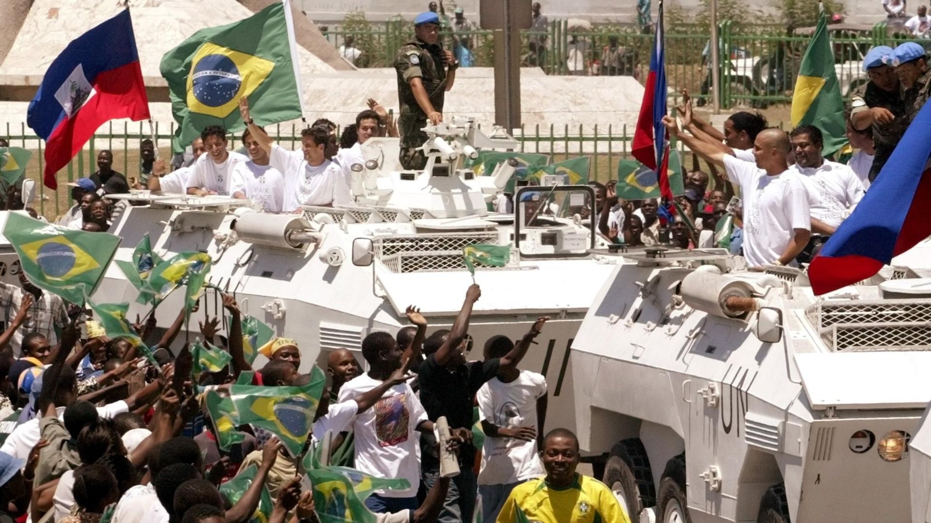 Jogadores da seleção brasileira acenam de dentro de tanques de guerra para os haitianos, antes do amistoso de 2004