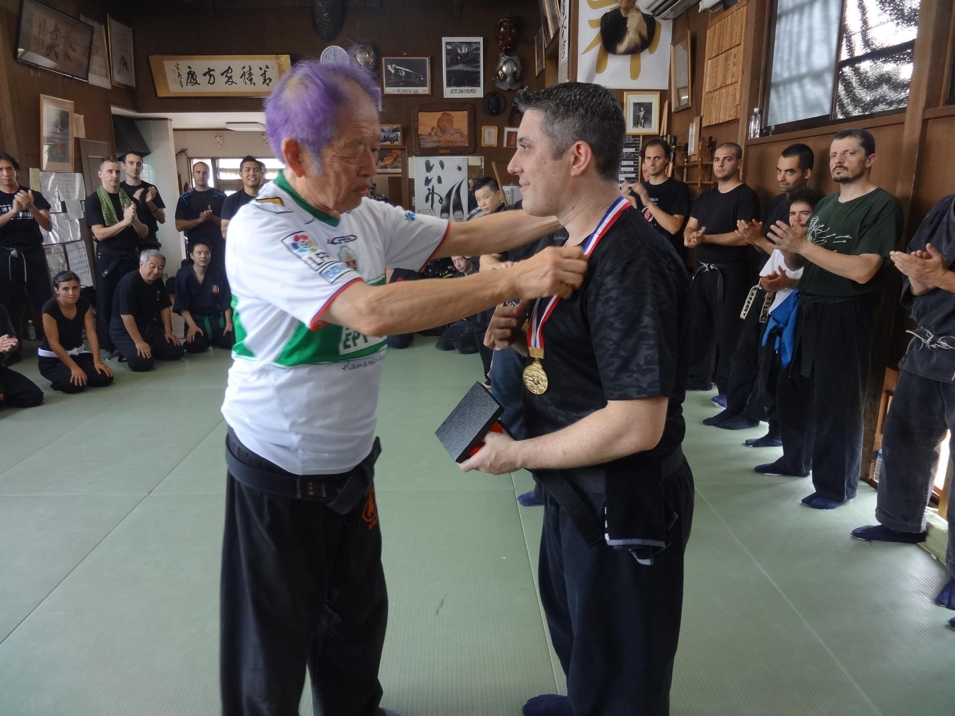 Hatsumi Masaaki, herdeiro de um clã ninja, entrega medalha a seu aluno brasileiro; o ninja japonês também é torcedor de futebol