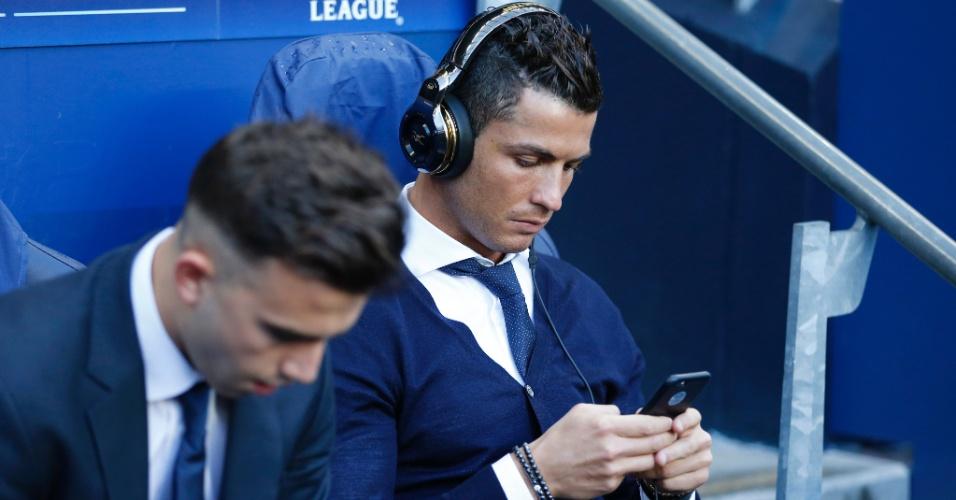 Cristiano Ronaldo usa o celular no banco de reservas que será destinado ao Real Madrid contra o Manchester City