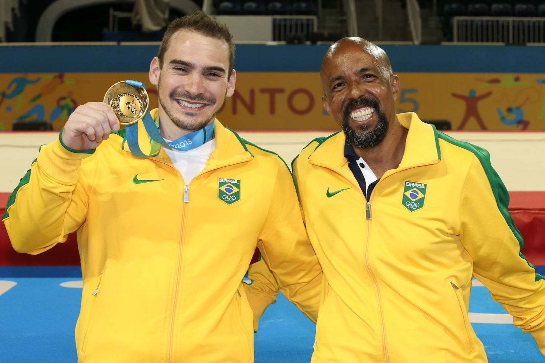 Arthur Zanetti e seu treinador exibem a medalha de ouro conquistada nas argolas
