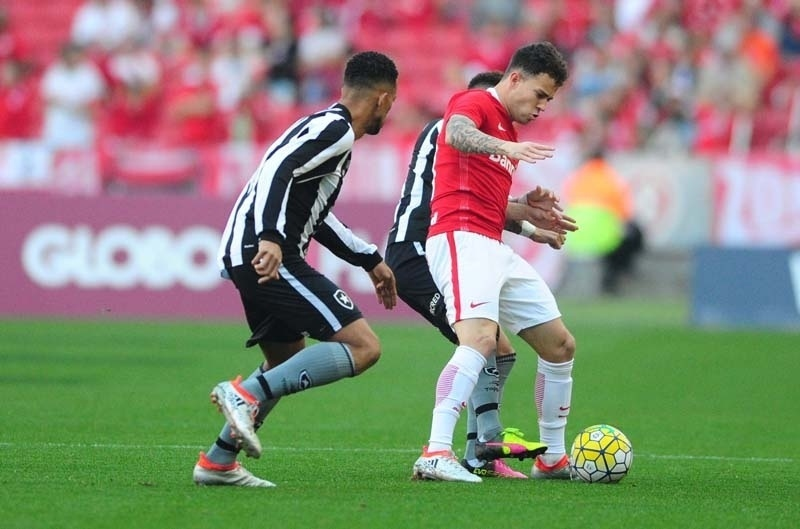 Gustavo Ferrareis encara a marcação na partida entre Internacional e Botafogo