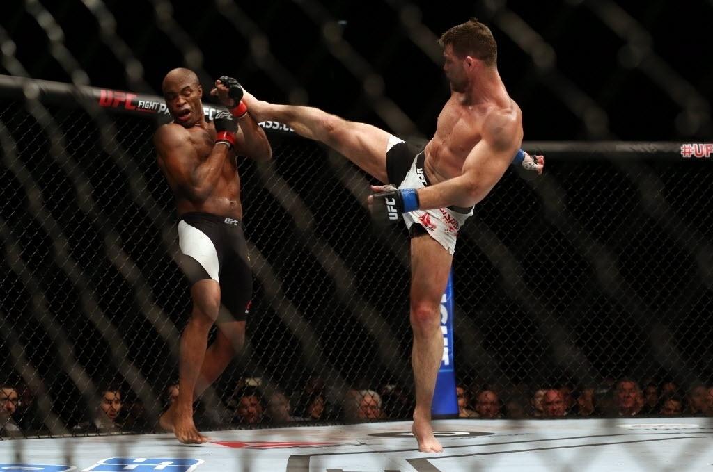 Anderson Silva tenta se defender de chute alto de Michael Bisping, na luta principal do UFC em Londres, neste sábado (27)