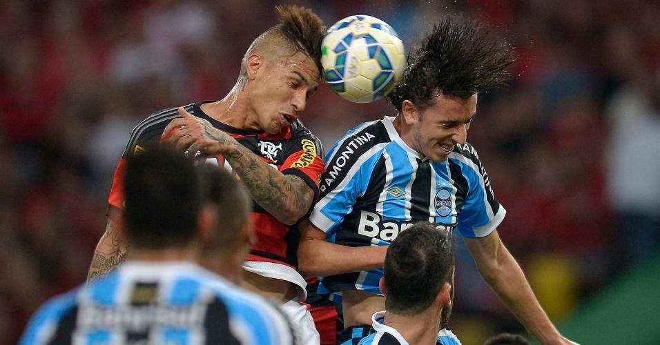Guerrero e Geromel disputam a bola durante o jogo Flamengo e Grêmio, no Maracanã