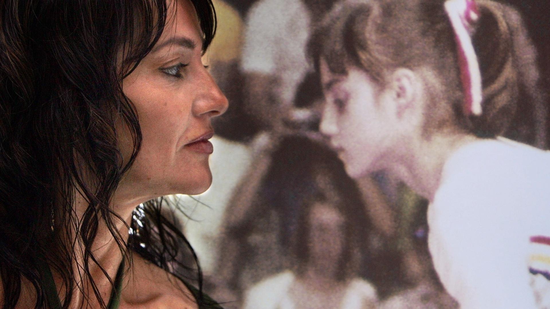 A romena Nadia Comaneci, ícone da ginástica, observa uma imagem dela mesma na época da primeira conquista dela em Jogos Olímpicos