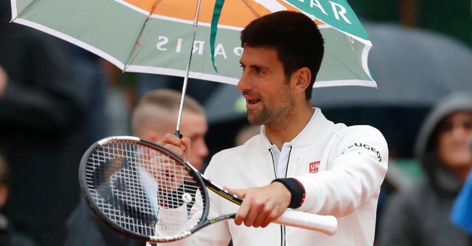 Djokovic com guarda-chuva após paralisação do jogo contra Bautista