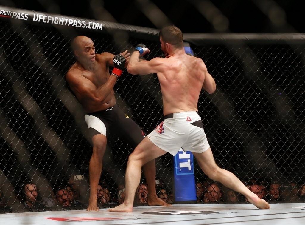 Anderson Silva (esq.) tenta se esquivar de golpe de Michael Bisping, na luta principal do UFC em Londres, neste sábado (27)
