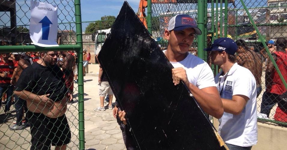 Funcionário carrega a porta do banheiro destruída em São Januário